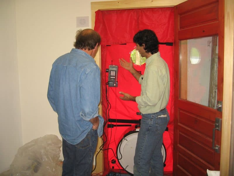 Blower door measuring air flow through house.